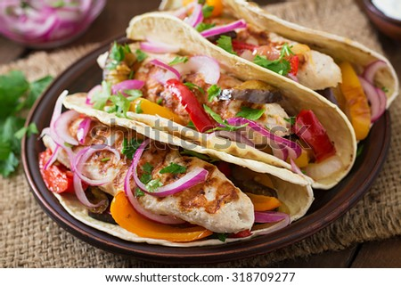 Mexican tacos with chicken, grilled vegetables and red onion. - stock photo