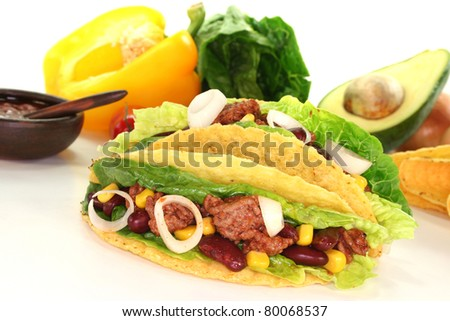 Mexican tacos with ground beef, lettuce, red kidney beans and corn on a white background - stock photo