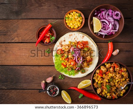 Mexican tacos with meat, corn and olives on wooden background. Top view - stock photo