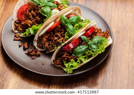 Mexican tacos with minced meat, beans and spices on a plate - stock photo
