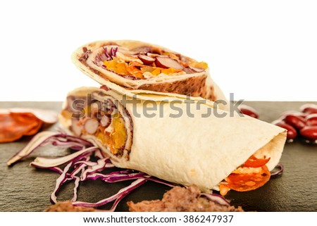Mexican Tortilla with Bean, Beef and Tomato. Wrap Cut in Half with Grilled Chicken and Red Cabbage Salad Salsa. Pork Hot Kulen Sausage Burrito Prawn Queiro Served on Black Board Plate. Tasty Fast Food - stock photo