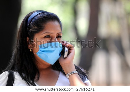 MEXICO CITY - APRIL 30:A woman talks on her cellphone while protecting herself against influenza with a face mask on April 30, 2009 in Mexico City. - stock photo