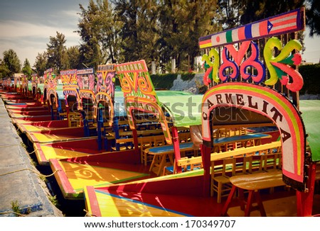 MEXICO CITY - MARCH 17: Colorful boats parked on a canal in Xochimilco Floating Gardens of Mexico on March 17, 2011 in Mexico City, Mexico. System of canals in Mexico City measures about 170 km. - stock photo