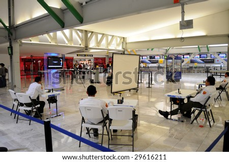 MEXICO CITY - MAY 1: Departing passengers are questioned about their health and screened for fever by officials  at the Benito Juarez Airport on May 1, 2009 in Mexico City. - stock photo