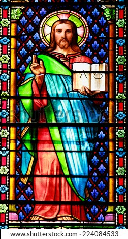 MEZE, FRANCE -July 23, 2014: Jesus with the Bible. Stained glass window in the Cathedral of Meze, South of France - stock photo