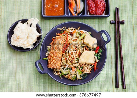 Mi goreng,mee goreng Indonesian cuisine, spicy stir fried noodles with tempeh and assortment of asian sauces Top view  - stock photo