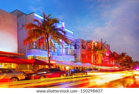 Miami Beach, Florida illuminated hotels and restaurants at sunset on Ocean Drive, world famous destination for nightlife, beautiful weather and pristine beaches - stock photo