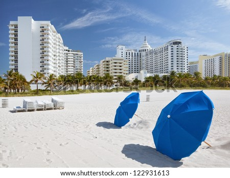 Miami Beach, Florida, sunny summer day, blue umbrellas and lounge chairs with modern architecture buildings. Famous travel location. - stock photo