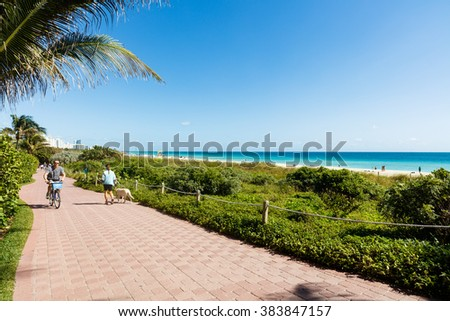 Miami Beach, Florida USA - February 25, 2016: Beautiful clear blue sky day in scenic and popular Miami Beach with beach goers along the promenade. - stock photo