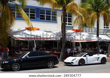 MIAMI BEACH - JUNE 19: Photo of luxury cars parked by curbside restaurants on Ocean Drive June 19, 2015 in Miami Beach FL - stock photo