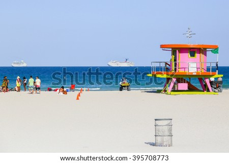 MIAMI BEACH, USA - MAY 9, 2015: A beach section with a pink lifeguard station and some people sitting or standing, a trash can in front and two cruise liners on the ocean in the back. - stock photo