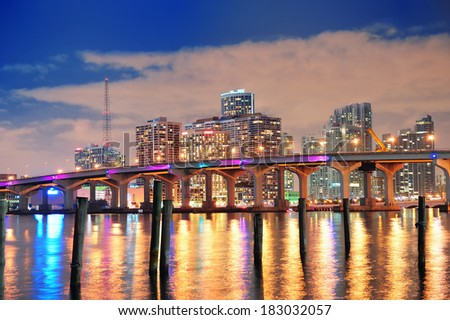 Miami city skyline panorama at dusk with urban skyscrapers and bridge over sea with reflection - stock photo
