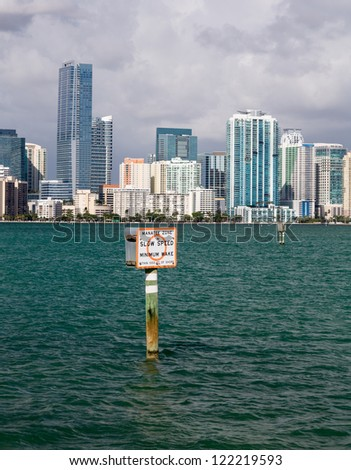 Miami cityscape skyline from Rickenbacker causeway on cloudy morning with Manatee zone slow speed sign - stock photo
