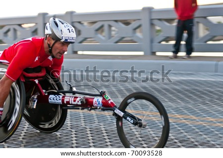 MIAMI, FL - JANUARY 30: Unidentified competitor races in a wheelchair during the Miami Marathon on January 30, 2011 in Miami, Florida. - stock photo
