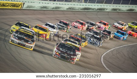 MIAMI, FL - Nov 16: Denny Hamlin (left) leading at the Nascar Sprint Cup Ford Ecoboost 400 race at Homestead-Miami Raceway in Homestead, FL on November 16, 2014 - stock photo