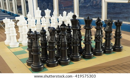 MIAMI, FL - NOV 21: Large outdoor chess board and chess pieces aboard the Carnival Breeze cruise ship, as it sets sail from Miami, FL, on Nov 21, 2015. The ship entered service on June 3, 2012. - stock photo