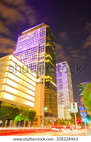 Miami Florida at sunset, colorful skyline of illuminated buildings and moving traffic - stock photo