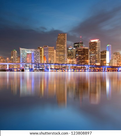 Miami Florida illuminated downtown buildings and bridge at sunset with reflections in the water of Biscayne Bay. Panoramic skyline of the World famous travel location. - stock photo