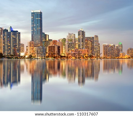 Miami Florida illuminated downtown buildings at sunset with reflections in the water of Biscayne Bay. Panoramic skyline of the World famous travel location - stock photo