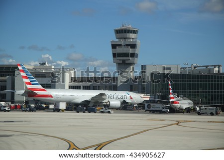 MIAMI, FLORIDA - JUNE 1, 2016: American Airlines plane and  Air Traffic Control Tower at Miami International Airport. American Airlines operates 274 flights every day from Miami - stock photo