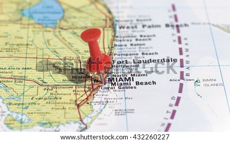 Miami marked on map with red pushpin. Selective focus on the word Miami and the bottom of pushpin. Pin is in an angle and casts some shadow to the left.  - stock photo