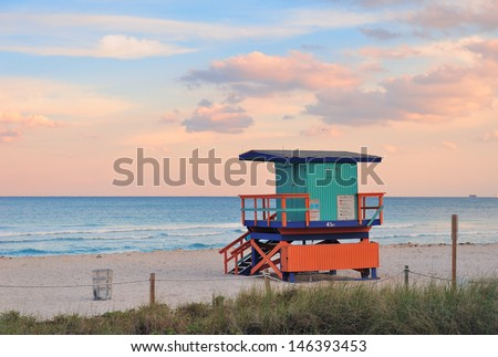 Miami South Beach sunset with lifeguard tower and coastline with colorful cloud and blue sky. - stock photo