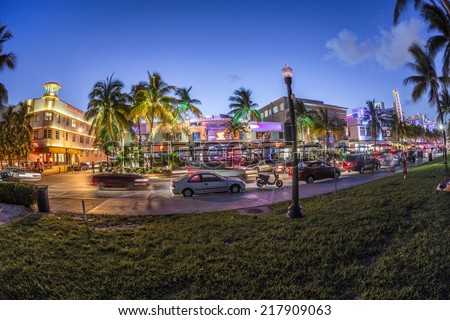 MIAMI, USA - AUG 23, 2014: Palm trees and art deco hotels at Ocean Drive by night. The road is the main thoroughfare through South Beach in Miami, USA. - stock photo
