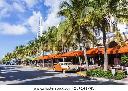 MIAMI, USA - AUG 5, 2013: The Art Deco Edison Hotel and a classic oldsmobile car on Ocean Drive, South Beach, Miami, USA. Classic cars are allowed to park at yellow line. - stock photo