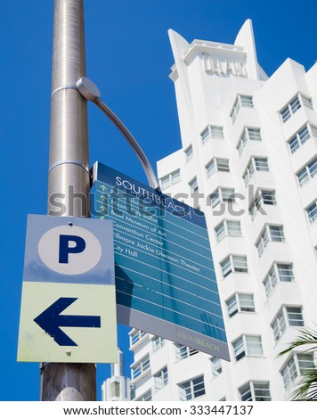 MIAMI,USA - AUGUST 8,2015 :  Street sign giving directions to Miami Beach landmarks with the famous Delano hotel on the background - stock photo