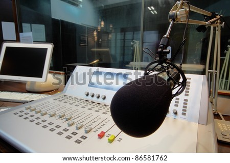 mic in front of the control panel in broadcasting studio - stock photo