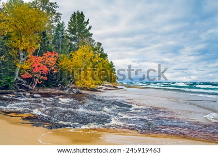 Michigan's Hurricane River flows across a sandy beach and into lake Superior in autumn at Pictured Rocks National Lakeshore. - stock photo