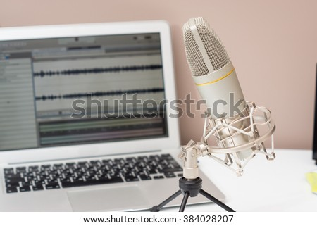 Microphone and a computer on a table in a studio. Sound recording theme image - stock photo