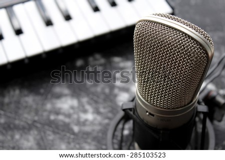 Microphone and blurred piano keys on background - stock photo
