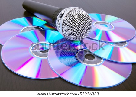 Microphone and dvd disks on black table,closed-up - stock photo