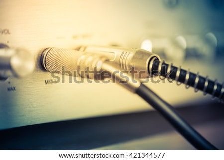 Microphone connectors plugged in a audio music mixing console. Vintage style photo and filtered process. - stock photo