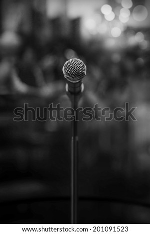 microphone in concert hall or conference room on a dark background - stock photo