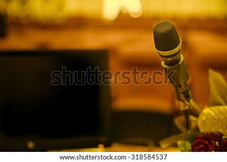 Microphone in concert hall or conference room with defocused bokeh lights in background. Extremely shallow dof - stock photo