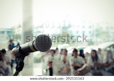 Microphone in concert hall or conference room with defocused person in background. , process in vintage style - stock photo