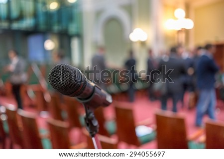 Microphone in focus against blurred chairs and standing talking audience - stock photo