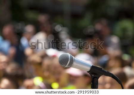 Microphone in focus against blurred group of people - stock photo