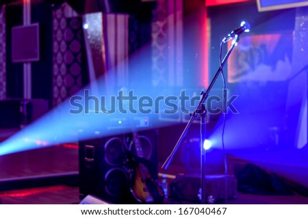 Microphone in smoke on a dark background and nightclub stage with colorful background - stock photo