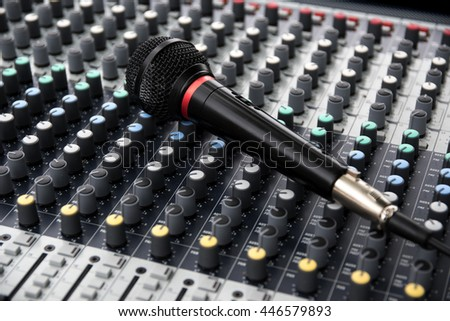 microphone on a professional sound mixing console with adjusting knobs, music device for audio signal, selected focus, narrow depth of field - stock photo