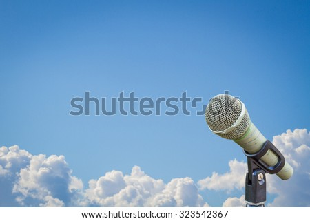 microphone on a stand over blurred cloudy blue sky, with wide copyspace - stock photo