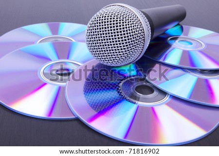 Microphone on compact discs, closeup on black table - stock photo