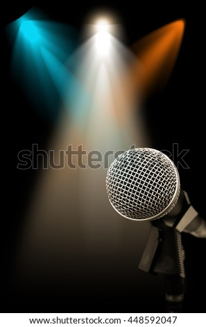 microphone on stage with colorful spotlight background - stock photo
