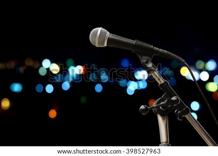 microphone on stand with bokeh light in city night time background - stock photo