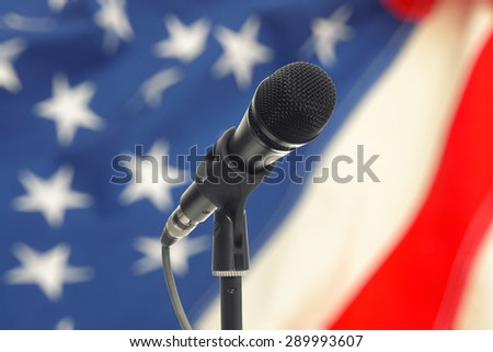 Microphone on stand with US flag on background - stock photo