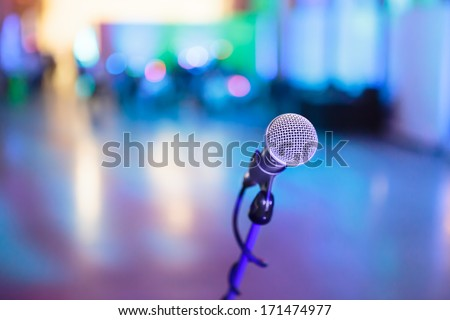 Microphone with blurred blue party stage around - stock photo