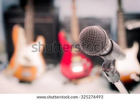 microphone with blurred musical instrument background, vintage style. - stock photo