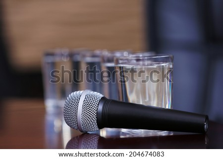 Microphone with glasses of water on table close-up - stock photo